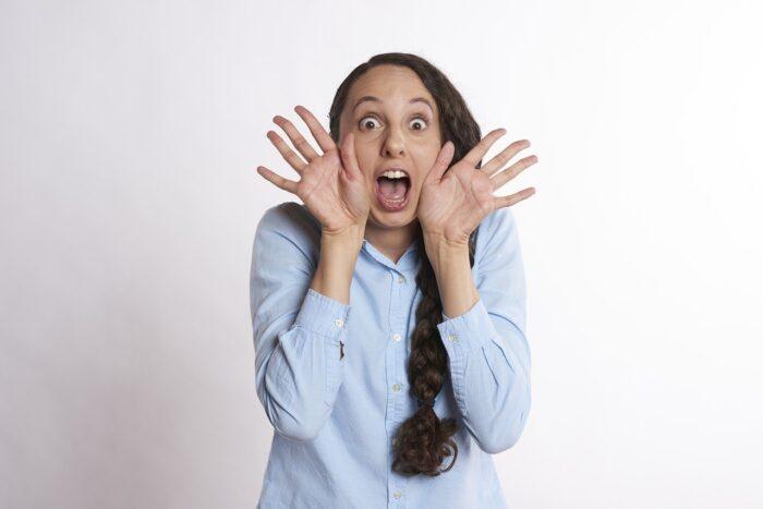 手を顔の横で広げながら驚いている女性